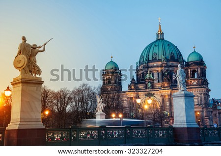 View of Evangelical Cathedral located on the Museum Island in Berlin, Germany. View of the bridge with statues at sunset. Clear sky - stock photo