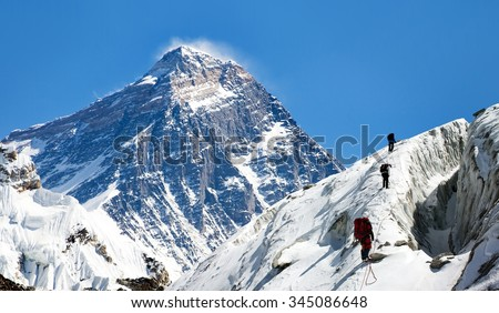 view of Everest from Gokyo valley with group of climbers on glacier, way to Everest base camp, Sagarmatha national park, Khumbu valley, Nepalese Himalayas - stock photo