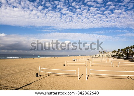 View of famous Huntington Beach volleyball courts during a beautiful, cloudy day.