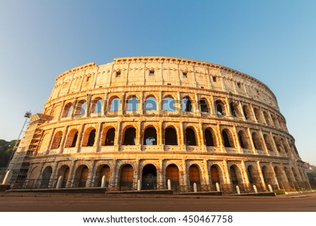 view of famous ruins of Colosseum at sunrise in Rome, Italy - stock photo