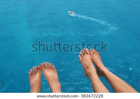 View of feet of couple parasailing with the speed boat in the sea background - stock photo