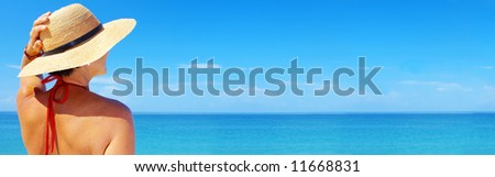 view of  female in sailor-hat on a background of the tropical sea. Banner, lots of copyspace. - stock photo
