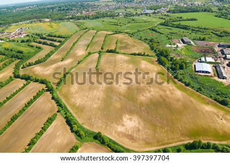 view of fields and meadows from height of bird's flight by eyes of the parachutist