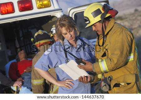 View of fire fighters and paramedics assisting injured man - stock photo