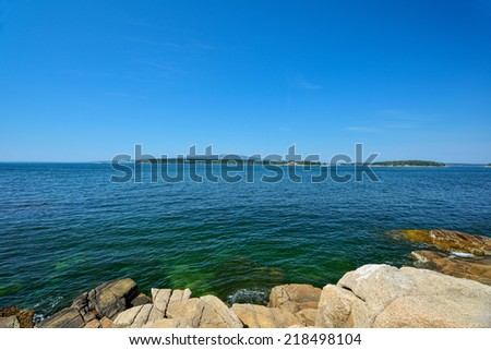 View of Frenchman's Bay filled with lobster floats and showing the pink granite rocks that make up the shoreline - stock photo