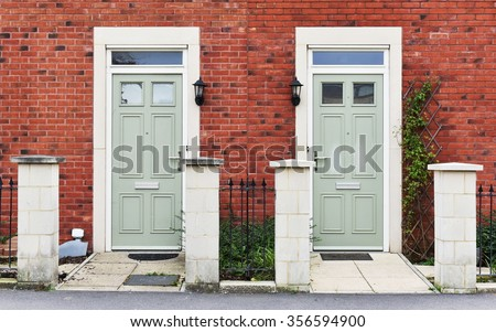 View of Front Doors of Two Neighbouring Red Brick English Town Houses on a Residential Estate - stock photo