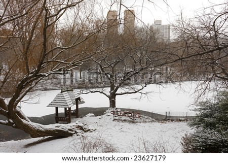 View of gazebo and the Lake in Central Park, New York City during a snowy, winter day, with the skyline of Manhattan in the background