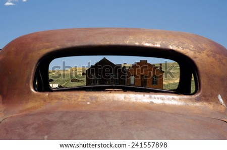 View of ghost town Bodie, CA through the back window of old car.  - stock photo