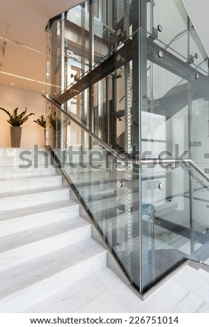 View of glass elevator in modern building - stock photo