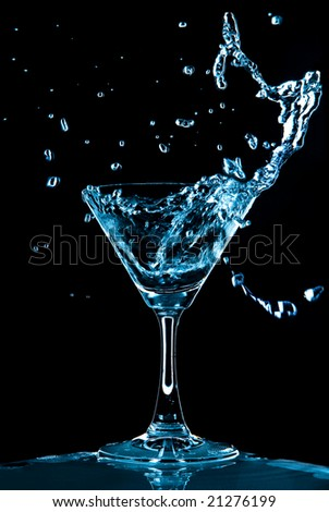 View of glass with Blue Curacao splash on black background - stock photo
