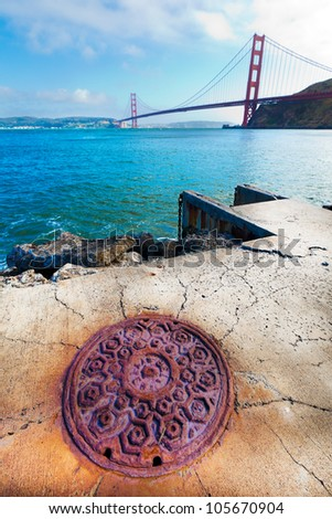 View of Golden Gate Bridge in San Francisco from across the water at Fort Baker in Sausalito.  Very old ornate manhole cover in the foreground. - stock photo