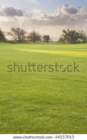 View of golf course with moody sunrise over English landscape - stock photo