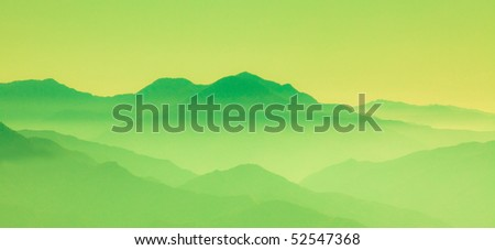 View of green mountains in the fog - stock photo