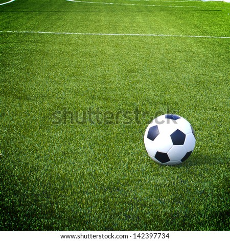 view of green striped football field with soccer ball - stock photo