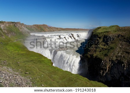 View of Gulfoss (Golden Falls) waterfall and tourists wandering around on a clear sunny summer day, Iceland - stock photo