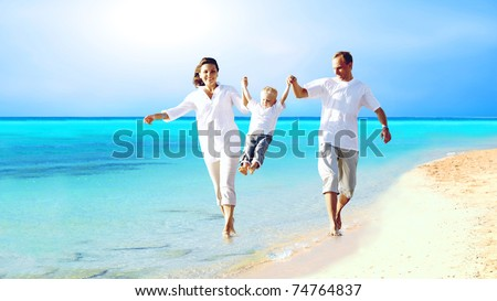 View of happy young family having fun on the beach - stock photo