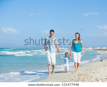 View of happy young family - mother, father and son having fun on the beach - stock photo