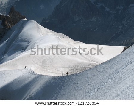 View of high Alps and few mountaineers on a snow slope. - stock photo