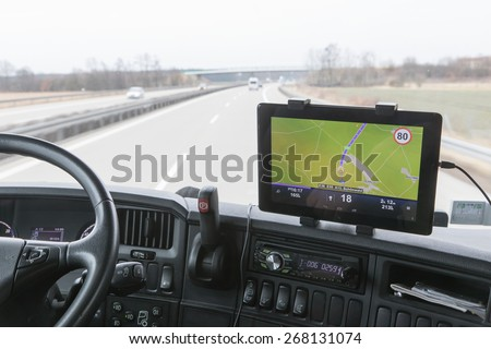 View of highway traffic through the windshield of the truck cab. Navigation is mounted on the dashboard. - stock photo