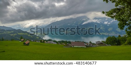 view of huts and Lake Thun on the slope of the forest-covered mountains in the Swiss Alps on a cloudy day. Beatenberg, Switzerland  Perfect background for a text