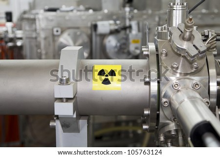 View of important electronic and mechanical parts of ION Accelerator, with high radiation sign, CNC machined parts - stock photo