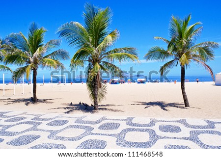 View of Ipanema beach with palms and mosaic of sidewalk - stock photo