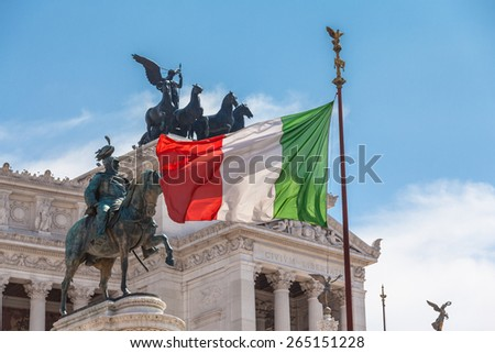 View of Italian national flag in front of Altare della Patria (Altar of the Fatherland) , the equestrian sculpture of Victor Emmanuel and statue of the goddess Victoria riding on quadrigas on top. - stock photo
