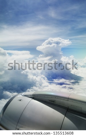 View of jet plane engine with cloud patterns - stock photo
