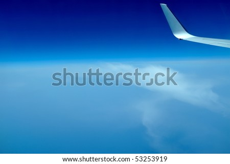 view of jet plane wing on the background of clouds and blue sky