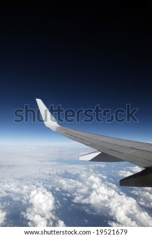 View of jet plane wing with cloud patterns and copy space - stock photo