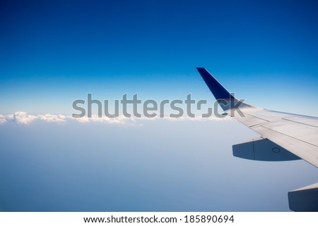 View of jet plane wing with crystal blue sky in the background and clouds with copy space.