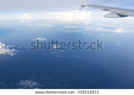 View of jet plane wing with crystal blue sky in the background and clouds with copy space. Amazaonas state, Colombia