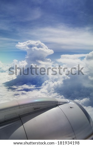 View of jet plane wing with giant cloud - stock photo