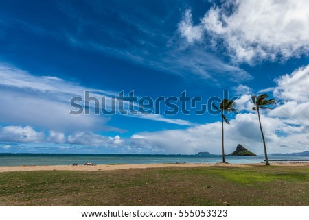View of Kaneohe Bay, Hawaii with Mokolii, commonly known as Chinaman 's Hat, and beautiful beach with visible reef and palm trees, and a tourist sunbathing