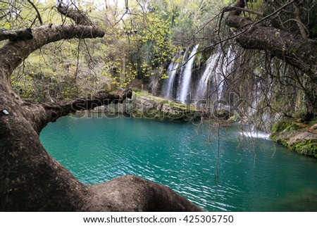 View of Kursunlu Waterfall in Antalya, flowing from high, with green trees and plants around. - stock photo