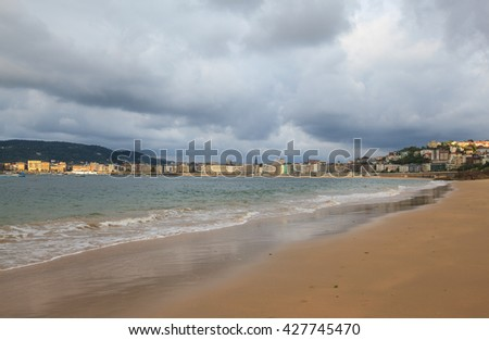 View of La Concha beach and city of San Sebastian in cloudy day, Basque Country, Spain  - stock photo
