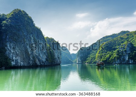 View of lagoon in the Halong Bay (Descending Dragon Bay) at the Gulf of Tonkin of the South China Sea, Vietnam. Beautiful landscape formed by karst towers-isles on blue sky background. - stock photo