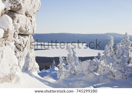 View of lake Zuratkul from Mountain range Zyuratkul, winter landscape. Snow covered spruces and rocks.