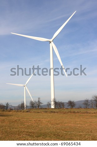 View of landscape with several windmills against blue sky generating power