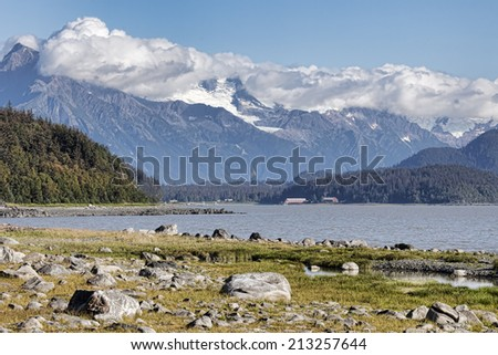 View of Letnikov Cove with an old cannery building surrounded by tall mountains. - stock photo