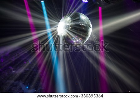View of light beams reflecting from a disco ball. - stock photo