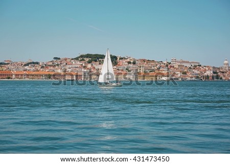 View of Lisbon skyline from across the river tagus with a sailing boat passing by