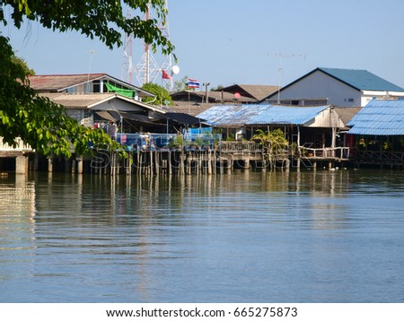 View of local houses reflected in the ocean under a blue sky at Laem Ngop in Trat Province, east Thailand