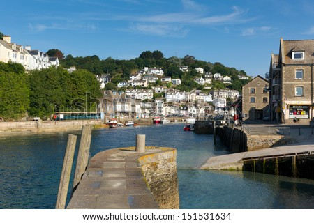 View of Looe harbour and river Cornwall England, with blue sea on a sunny summer day and town on the hillside - stock photo