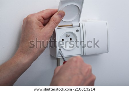 View of man's hands during electric socket repair