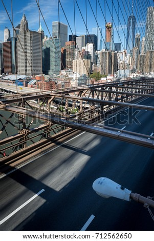 View of Manhattan skyline seen from Brooklyn bridge in bright day light blue sky, New York