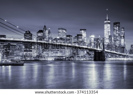 View of Manhattan with skyscrapers and old Brooklyn Bridge by night, New York City illumination - stock photo