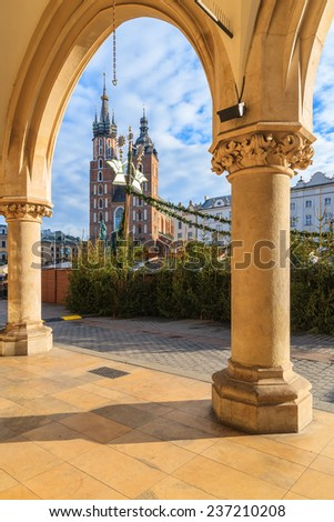 "View of Mariacki church from Cloth Hall building ""Sukiennice"" on main market square of Krakow city during Christmas fairs, Poland - stock photo"