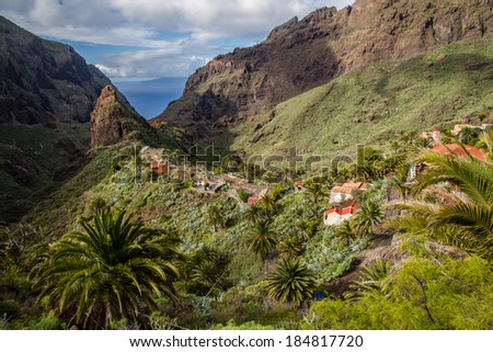 View of Masca Village with Palms, Mountains and Ocean in the background - Masca,Tenerife, Canary Islands, Spain - stock photo