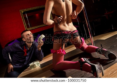 View of men offering money to a stripper on stage - stock photo